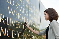 Girl looking at inscription of marine corps war memorial