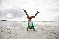 Young man doing cartwheels on beach