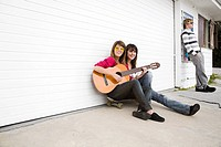 Two girls sitting on floor with guitar