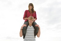 Young couple, man carrying girl on shoulders