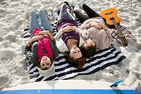 Three girls lying on beach with guitar