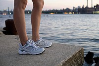 Legs and shoes of runner by river