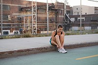 Female runner sitting on sidewalk