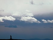 Tibetan woman praying under sheltering sky, Tagong Grassland, DiQing Tibetan Autonomous Prefecture, Yunnan Province, China