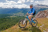 Man mountain biking at Crepe De Zumeles near Rifugio Son Forcia below Cima De Meso Cristallo high above the city of Cortina in northern Italy