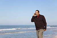 Man talking on cell phone while walking on beach