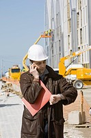 Building contractor using cell phone, checking time