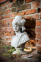 Stone statue of a girl near a brick wall