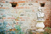 Young girl statue along brick wall