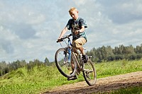 Teenage Boy Riding Bicycle and Doing Action Trick