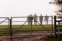 group of walkers approching metal countryside gate from the mist