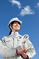 Woman in hardhat with blueprint