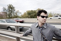 Young man standing by a highway