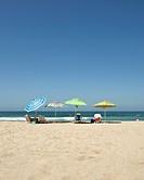 four beach umbrellas lined up on beach