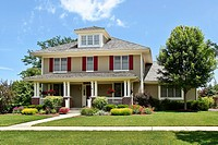 Suburban home with front porch and red shutters