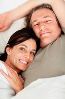 Happy relaxed mature couple lying in bed