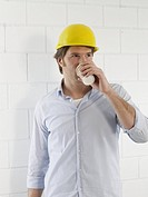 Man wearing a helmet is drinking coffee