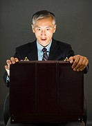 Surprise businessman looking into open briefcase, studio shot