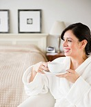 Hispanic woman in bathrobe drinking coffee in bedroom
