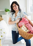 Smiling Hispanic woman carrying basket of laundry