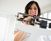 Smiling Hispanic woman weighing herself on scale