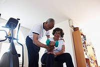Black man helping wife with hand weights