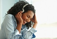 Black woman listening to headphones