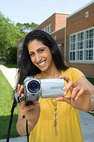 Young woman with video camera, camcorder, outside of school in Winnipeg, Manitoba, Canada.