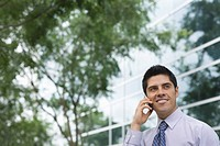 Hispanic businessman using cell phone outdoors