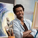 Smiling Black artist with arms crossed