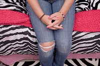 Teen girl sitting on bed with torn blue jeans