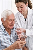 Geriatric care. Young woman helping an older man to take his medication.