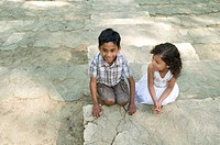 Two siblings, a 5_year_old Indian boy and a 4_year_old Guatemalan girl, on historic, stone steps at the Forest Theater in Chapel Hill, North Carolina,...