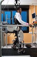 Lokomat walking therapy. Female patient on a treadmill, using the Lokomat therapy system. This consists of a robotic gait orthosis leg braces, white a...