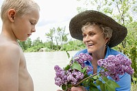 Little boy giving grandmother flowers