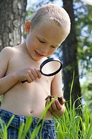 Little boy examining some dirt with a magnifying glass