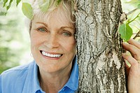 Senior woman beside a tree