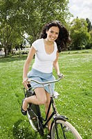 Young woman riding bicycle in grass