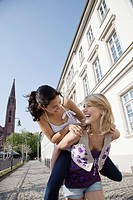 Young woman giving friend piggyback ride