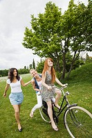 Young women riding bicycle in grass