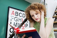 Young redheaded woman reading book