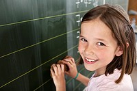 Girl standing by blackboard