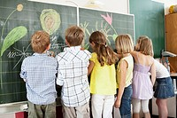 Children writing and drawing on blackboard (thumbnail)