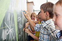 Children writing on blackboard