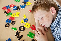 Boy lying next to alphabet letters