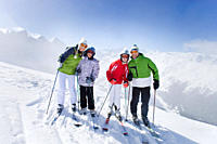 Family of skiers smiling together on mountain top