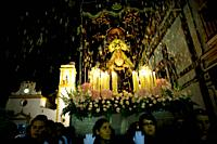 People throw flowers toward a wooden statue of the Virgin of Pain as she is publicly displayed in a Holy Week procession in the town of Prado del Rey ...