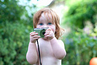 A young child holding a camera, outdoors