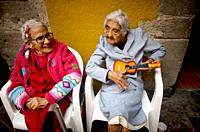 Isabel Minor Alarcon, 99, right, jokes holding her toy guitar as Luz Maria Rodríguez, 92, looks on in Our Lady of Guadalupe Home for the Elderly, Mexi...