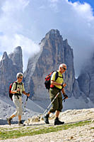 Couple of elderly mountain walkers in front of the Tre Cime di Lavaredo / Drei Zinnen, Dolomites, Italy